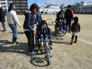 (写真)ハンドサイクル2台が並んでいます。子どもが乗っているところ
