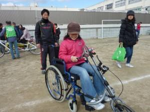 (写真)ハンドサイクルに女の子が乗っているところ。後ろから先生が見守っています