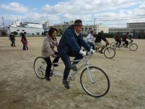 (写真)タンデム自転車がグラウンドを走っているところ。3台映っています