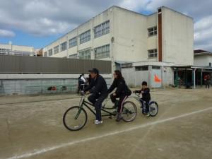 (写真)3人乗りのタンデム自転車です。一番前はパイロットのボランティアさん、真ん中はお母さん、一番後ろはお子さん