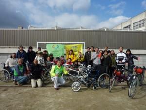 (写真)サッカーゴールに旗をぶら下げて、その前にパイロットや参加者、さらにその前に自転車を並べて記念撮影しています