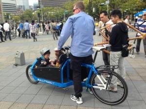 (写真)前に荷台のある自転車、カーゴバイクに2人の子どもを乗せている人