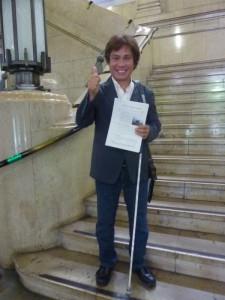 (写真)大阪府庁正面入り口スグの階段前で意見書を持つ鈴木会長