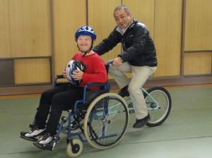(写真)車椅子取付タイプの自転車に挑戦 おとなががんばって漕いでいます