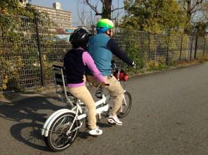 (写真)武庫川河川敷をタンデム自転車が走っているところ