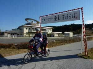 (写真)「ツアー・オブ・奈良・まほろば」と書かれたゲートを通過するタンデム自転車