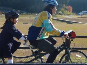 (写真)競輪選手の後ろに小学生が乗車してタンデム自転車をこいでいます