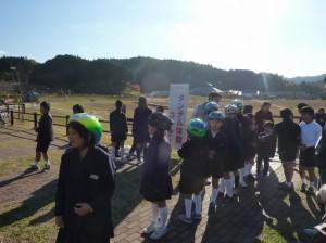 (写真)小学生がヘルメットをかぶって、順番待ちしています。