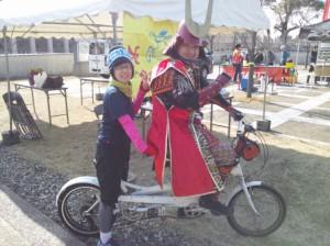 (写真)タンデム自転車の乗る甲冑を来た人