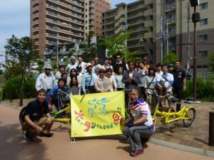 (写真)大阪でタンデム自転車を楽しむ会の旗を持って、みんなで記念撮影
