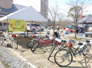 (写真)大阪でタンデム自転車を楽しむ会のテントの前にタンデム自転車が並んでいる