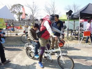 (写真)親子でタンデム自転車に乗る