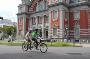 (写真)タンデム自転車が中央公会堂の前を走っている