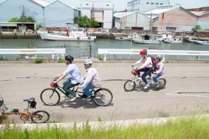 (写真)福漁港の前をタンデム自転車が走っている