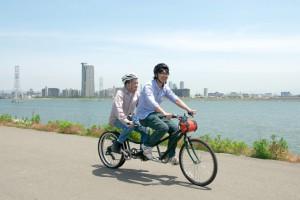 (写真)タンデム自転車の後ろには淀川、その後ろには梅田のビルが見えます