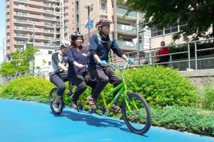 (写真)3人乗り自転車が出発。真中がお母さん、一番後ろが息子さん