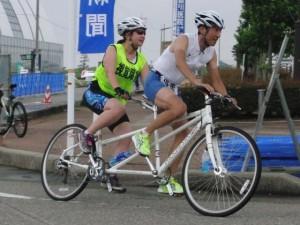 (写真)タンデム自転車で走るスポーツ部の大西監督(前)と山田選手(後ろ)