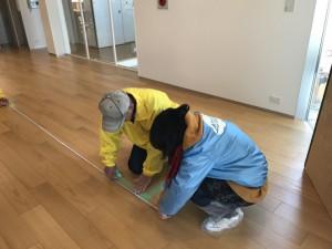 メジャーで床を測っている様子の写真