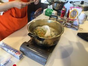 ポリ袋に入れたご飯とカレーの材料をお湯をはった鍋にいれます